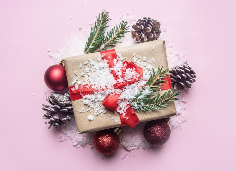 Nowego Roku pojęcie, pudełko z prezentem, choinek zabawki rozkłada na różowym tle z śnieżnym mieszkaniem nieatutowym obraz royalty free