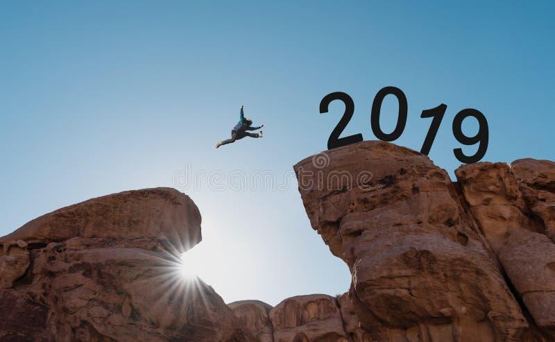 Nowego roku pojęcie, sylwetka mężczyzny doskakiwanie przez falezę 2019 fotografia royalty free