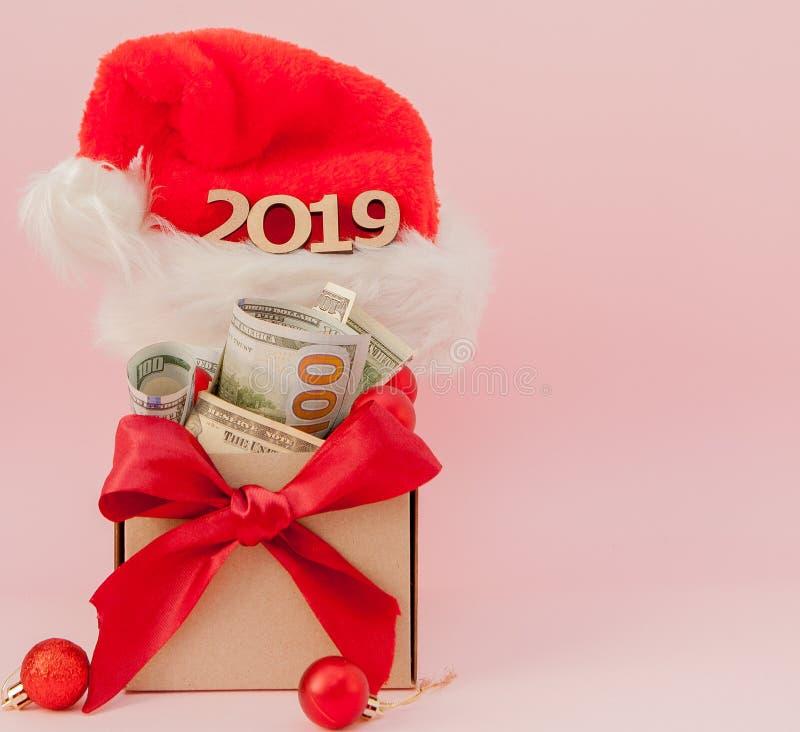 Nowego roku prezenta pudełko z dolarami i inskrypcja 2019 na różowym tle fotografia stock