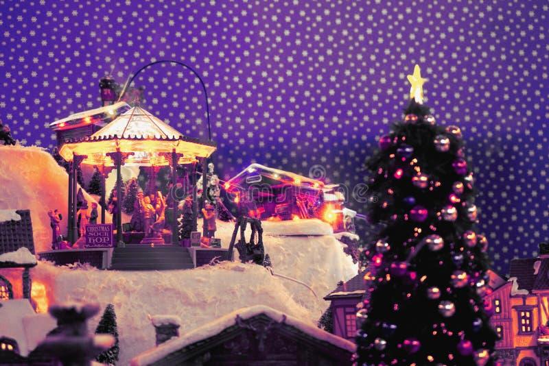 Nowego Roku ` s miasto w miniaturze z carousel dla dzieci, choinka, śnieżne drogi Rama kolory: fiołek, purpura, biel, kolor żółty obraz royalty free