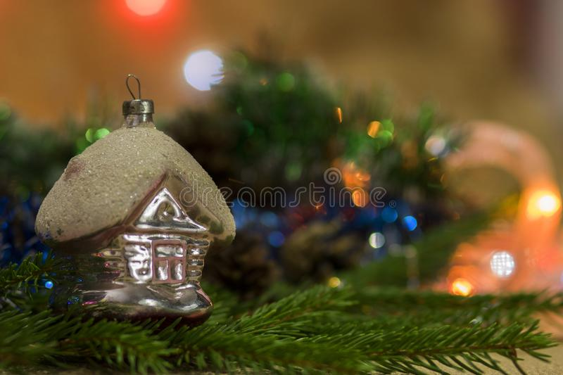 Nowego Roku ` s zabawka - dom na świerczyn gałąź z bokeh w tle i obrazy stock