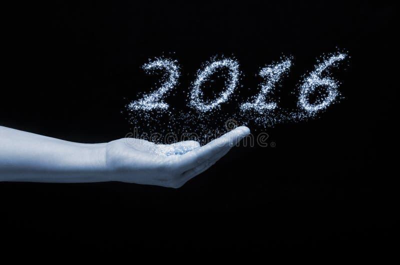 Nowego roku 2016 writing błyska fajerwerk trzyma dalej ludzką rękę z czarnym tłem zdjęcie stock