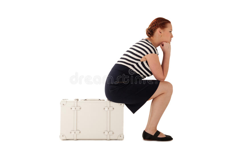Nowhere to go. Woman is lost and sitting on suitcase thinking where to go then stock photo