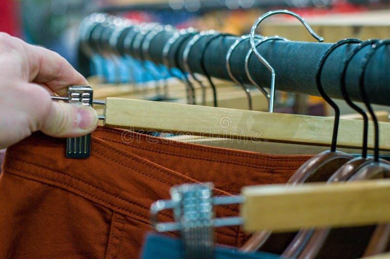 Nowi spodnia na wieszakach w sklepie Sprzedaże detaliczne centrum handlowe centrum wewnętrzny zakupy nowe ubrania Tło kolorowy pr obraz royalty free