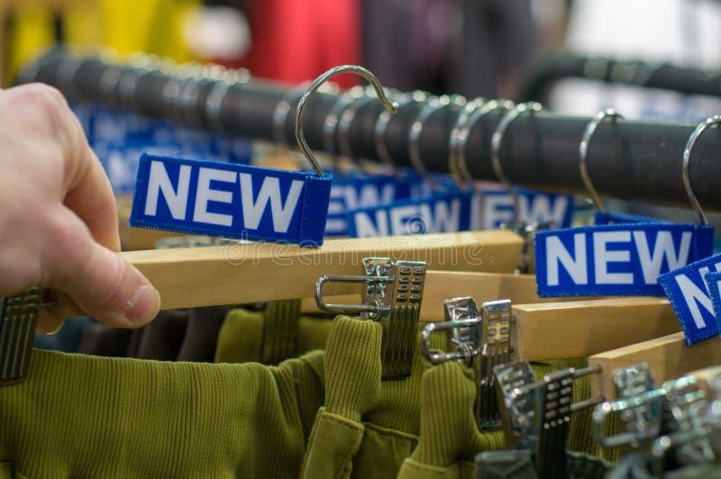 Nowi spodnia na wieszakach w sklepie Sprzedaże detaliczne centrum handlowe centrum wewnętrzny zakupy nowe ubrania Tło kolorowy pr zdjęcie stock