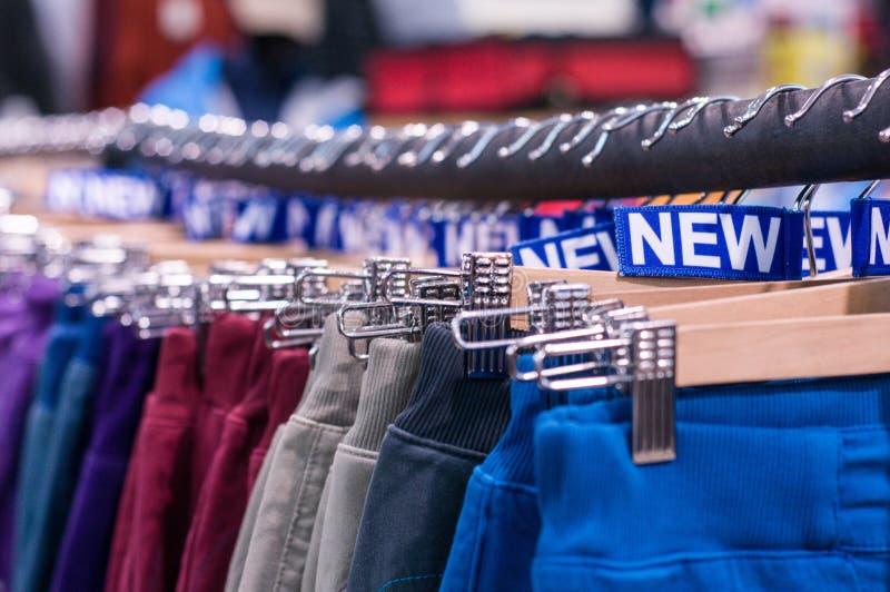 Nowi spodnia na wieszaku w sklepie Sprzedaże detaliczne centrum handlowe centrum wewnętrzny zakupy nowe ubrania Tło kolorowy proj zdjęcia stock