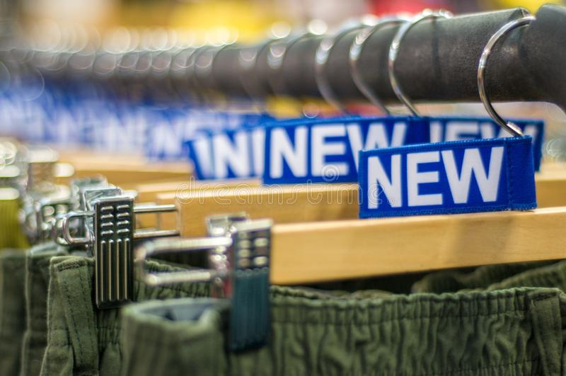 Nowi spodnia na wieszaku w sklepie Sprzeda?e detaliczne centrum handlowe centrum wewn?trzny zakupy nowe ubrania T?o kolorowy proj zdjęcie royalty free