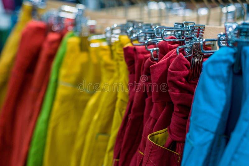 Nowi spodnia na wieszaku w sklepie Sprzeda?e detaliczne centrum handlowe centrum wewn?trzny zakupy nowe ubrania T?o kolorowy proj zdjęcia stock