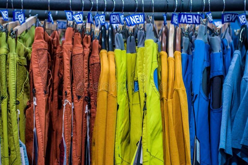 Nowi spodnia na wieszaku w sklepie Sprzeda?e detaliczne centrum handlowe centrum wewn?trzny zakupy nowe ubrania T?o kolorowy proj fotografia stock