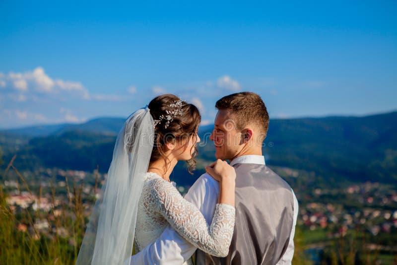 Nowożeńcy uśmiechają się each inny wśród łąki i ściskają na górze góry Ślubny spacer w drewnach w górach delikatny zdjęcia stock