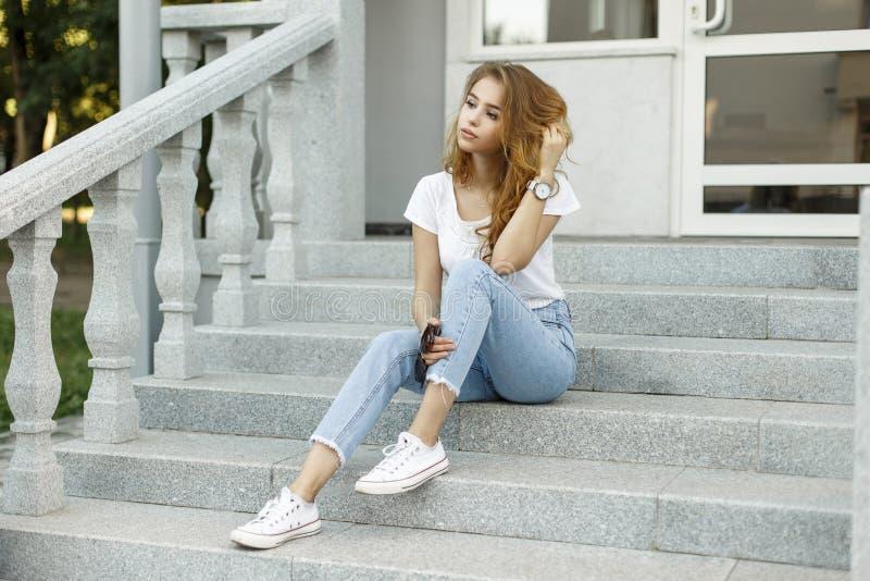 Nowożytna atrakcyjna elegancka młoda kobieta odpoczywa siedzieć w modnej koszulce w niebieskich dżinsach w białych sneakers fotografia royalty free
