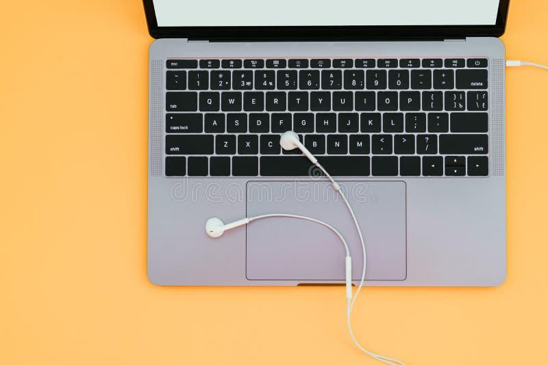 Nowożytny kruszcowy laptop i biali hełmofony odizolowywający na tle żółtym copyspace i, odgórny widok obraz stock