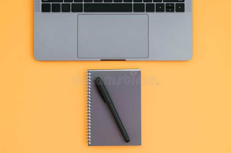 Nowożytny laptop i notepad z piórem odizolowywającym na pomarańczowym tle Mieszkanie nieatutowy fotografia stock