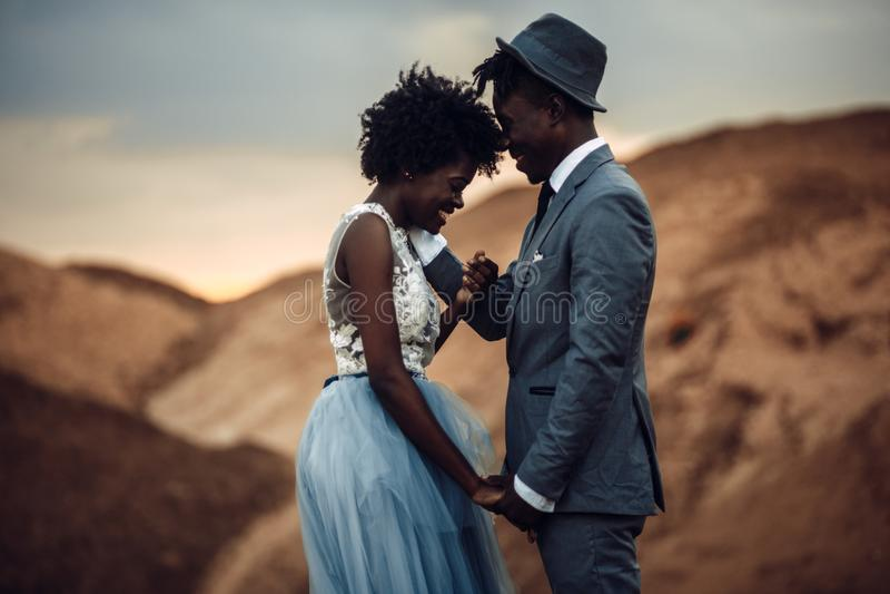 Nowożeńcy chwyta ręki, śmiech i stojak przeciw pięknemu krajobrazowi, fotografia stock