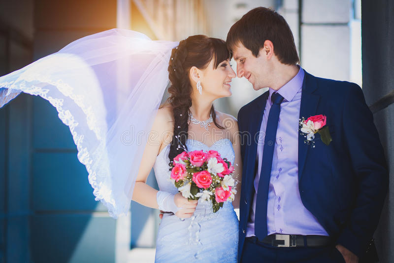 Nowożeńcy przeciw błękitnemu nowożytnemu budynkowi zdjęcie royalty free
