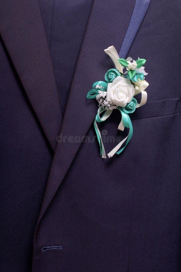 Nowożena ` s kostium wiesza na wieszaku Na klatce piersiowej dołączającej ślubny kwiat fotografia stock