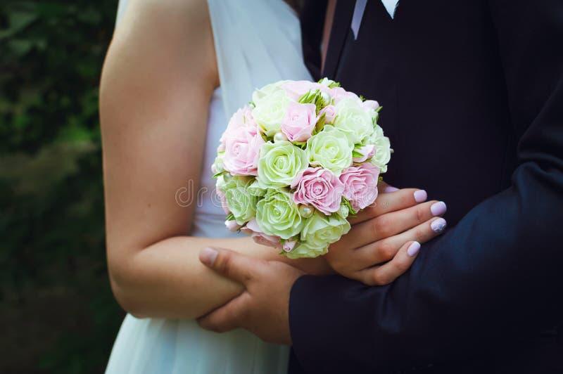 Nowożeniec obejmuje panny młodej na jej dzień ślubu Panny m?odej ` s bukiet Zako?czenie zdjęcie stock