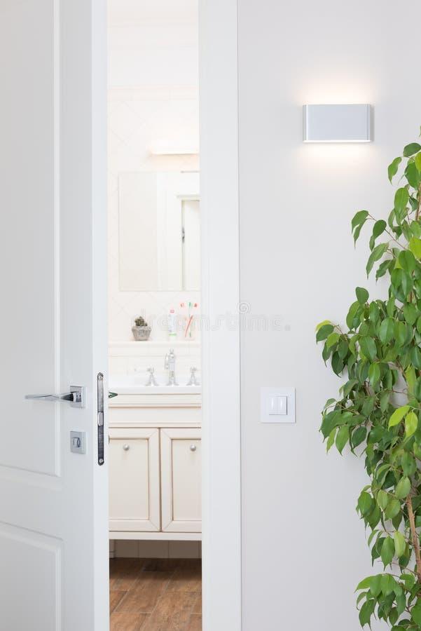 Nowożytna ścienna lampa, jaskrawy biały wnętrze Drzwi odchylony półdupki fotografia stock