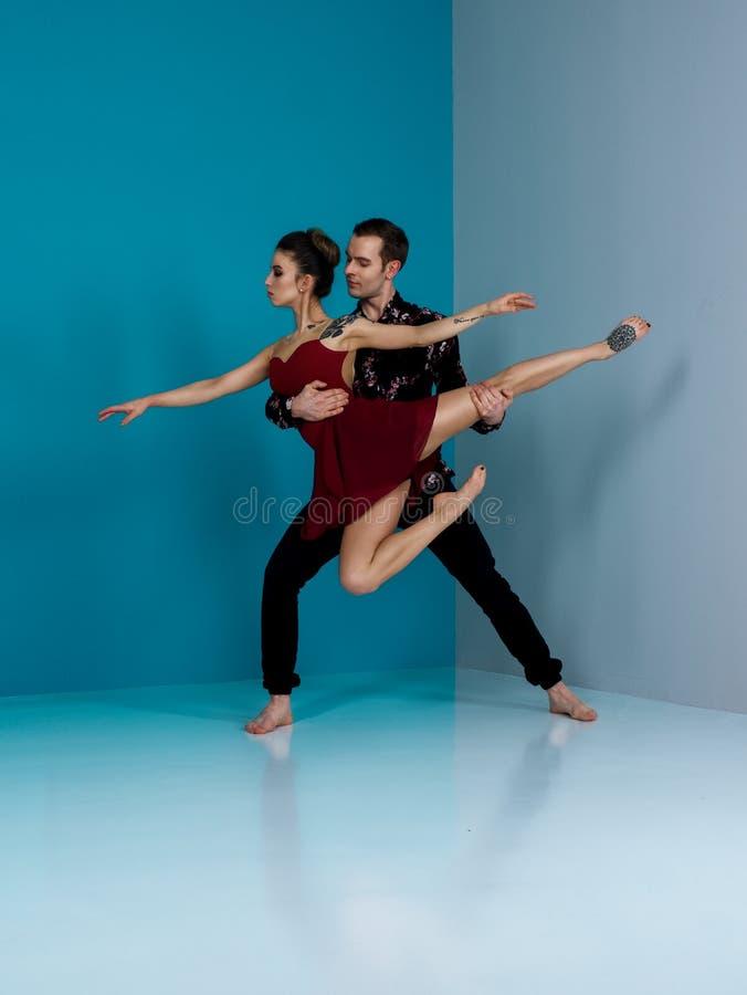 Nowożytna baletniczego tancerza para w czarnym spodniowym czerni w róży koszula i bordo przedstawienia tana smokingowym elemencie fotografia stock