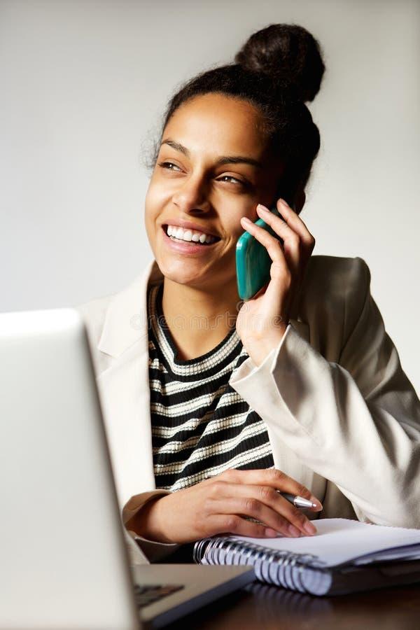 Nowożytna biznesowa kobieta ono uśmiecha się i opowiada na telefonie komórkowym fotografia royalty free