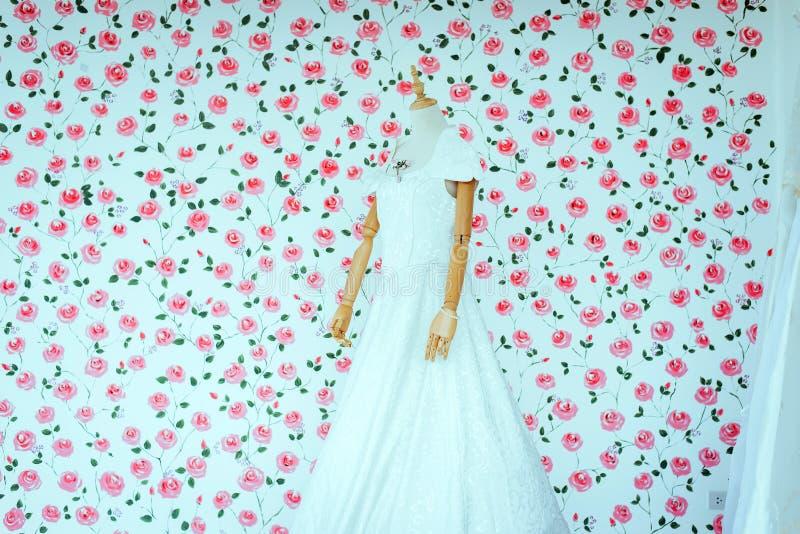 Nowożytna długa biała ślubna suknia na mannequin z blured menchiami kwitnie tło obraz stock