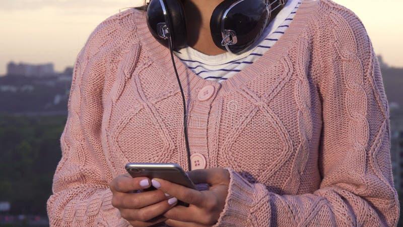 Nowożytna dziewczyna pisać na maszynie coś na jej smartphone zdjęcia royalty free