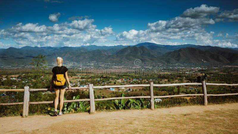 Nowożytna dziewczyna z tatuażami patrzeje z góry pięknego widok miasto Pai Jest ubranym drelich i plecaka zdjęcie stock