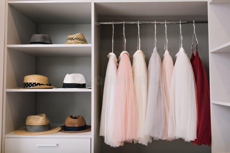 Nowożytna jaskrawa przebieralnia z półkami Modni kapelusze, piękne menchie i czerwieni suknie wiesza w garderobie, zdjęcia royalty free