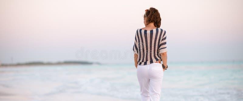 Nowożytna kobieta na seashore przy zmierzchu odprowadzeniem obrazy royalty free