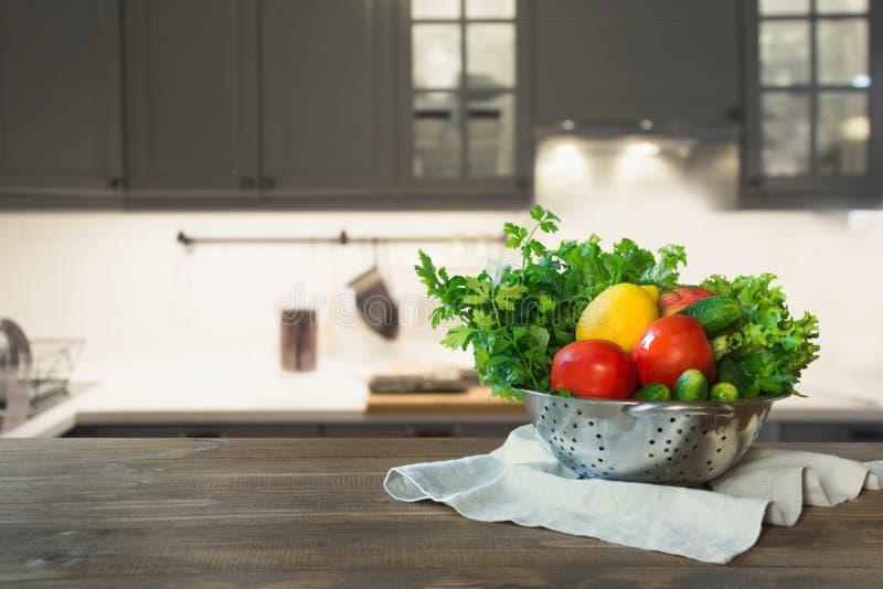 Nowożytna kuchnia z świeżymi warzywami na drewnianym tabletop, przestrzeni dla ciebie i pokazów produktach, obrazy stock