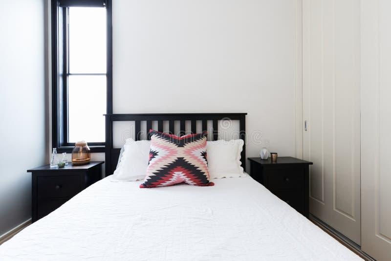 Nowożytna lekka jaskrawa sypialnia z potrząsacza łóżkiem i białą pościelą zdjęcie stock