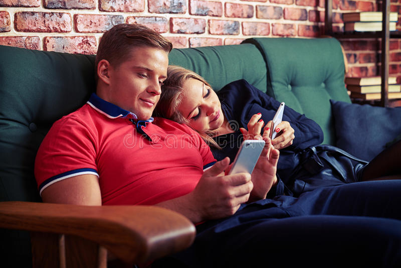 Nowożytna para używa telefon komórkowego podczas gdy siedzący ignorujący each oth fotografia stock