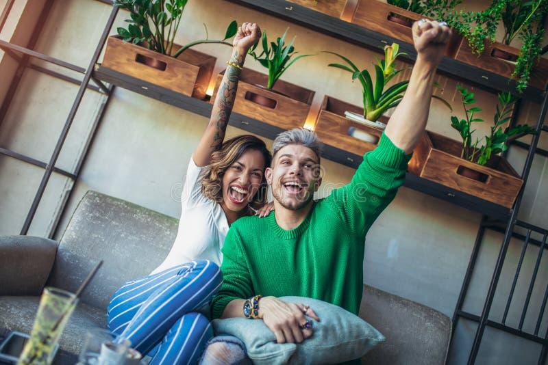 Nowożytna para w cukiernianym przyglądającym futbolowym dopasowaniu na tv w kawiarni obrazy royalty free