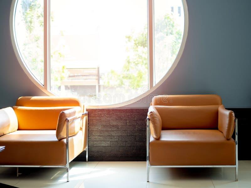 Nowożytna pomarańczowa rzemienna kanapa na błękitnym tle z round okno zdjęcia stock
