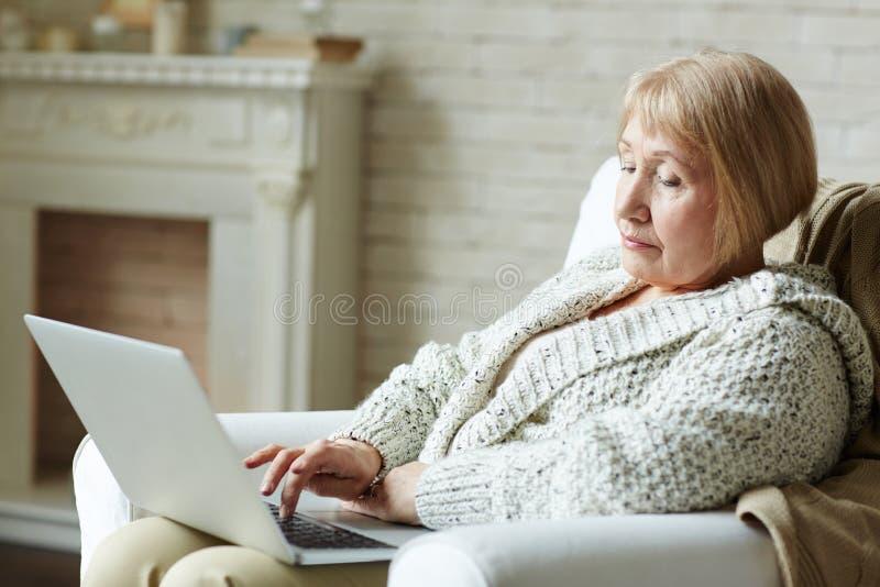 Nowożytna starsza kobieta surfuje sieć obraz royalty free