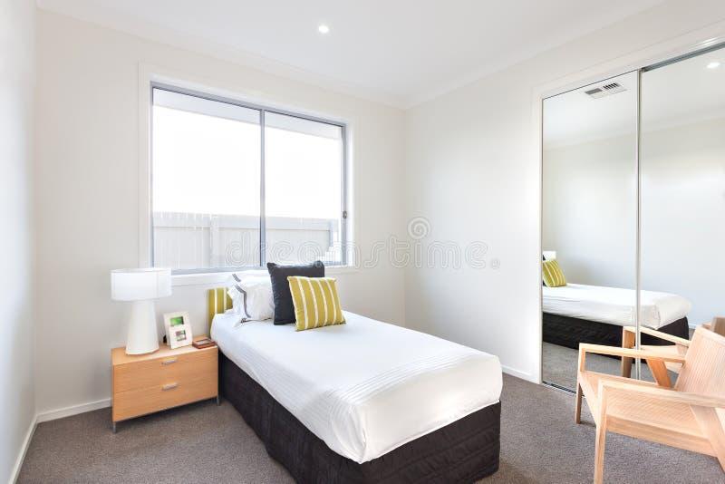 Nowożytna sypialnia z pojedynczym łóżkiem bielem i ciąć na arkusze blisko lustra fotografia stock