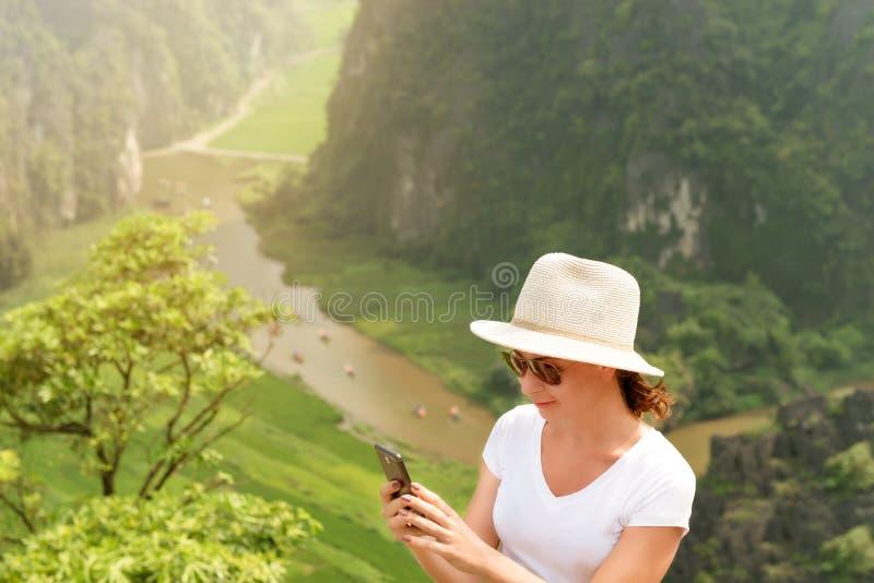 Nowożytna technologia i komunikacja wycieczkuje i trekking pojęcie Młoda kobieta używa smartphone na wierzchołku szczyt fotografia stock