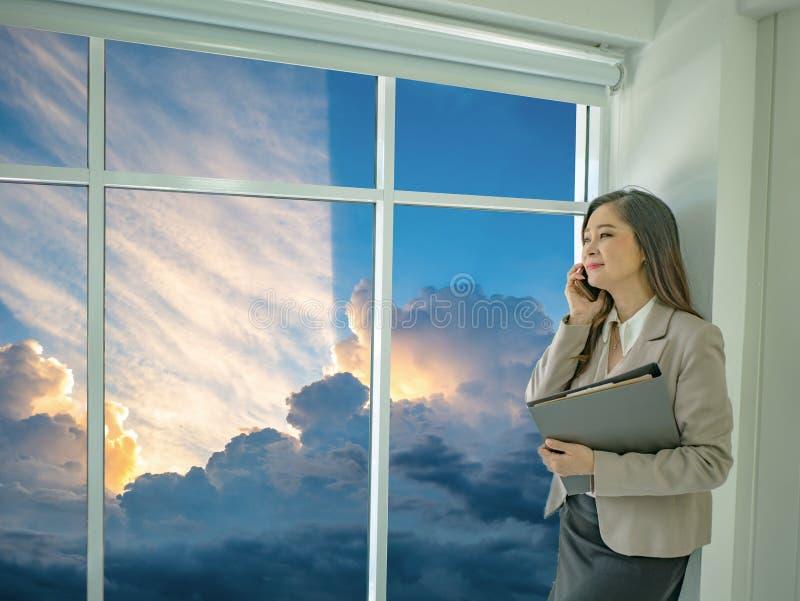 Nowożytne biznesowe kobiety używają telefon komórkowego podczas gdy patrzejący idyllicznego s zdjęcia stock