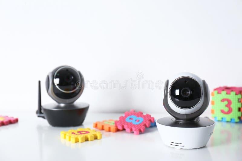 Nowożytne CCTV kamery bezpieczeństwe, dziecko i intrygują na stole przeciw białemu tłu fotografia royalty free