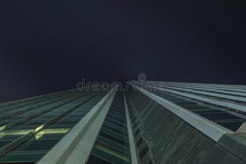 Nowożytne szklane sylwetki drapacz chmur przy nocą obrazy stock