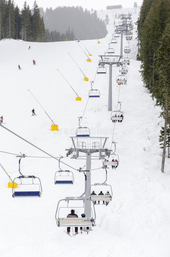 Nowożytnego krzesła narciarski dźwignięcie w ośrodku narciarskim i ludziach narciarstwa w tle zdjęcia stock