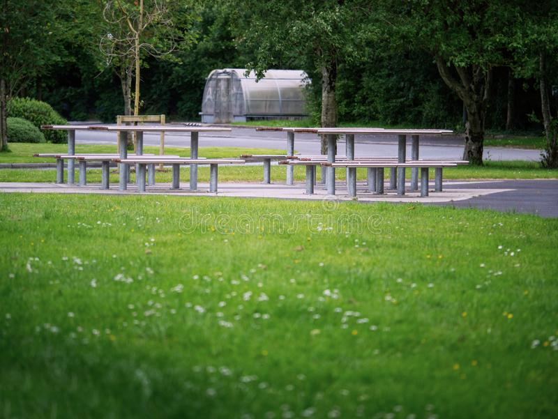 Nowożytni metali stoły w parku, Pykniczny lunchu teren Nikt, Zielona trawa i drzewa, fotografia royalty free