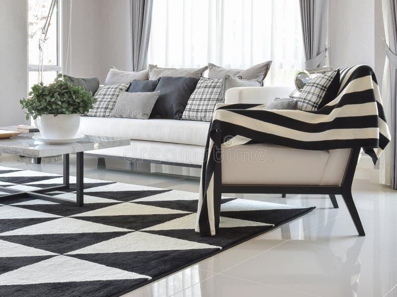 Nowożytny żywy izbowy wnętrze z czarny i biały sprawdzać deseniowymi poduszkami i dywanem zdjęcia stock
