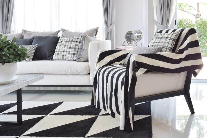 Nowożytny żywy izbowy wnętrze z czarny i biały sprawdzać deseniowymi poduszkami i dywanem fotografia royalty free