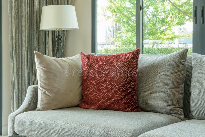 Nowożytny żywy pokój z czerwonymi poduszkami na szarej kanapie i dekoracyjnej lampie w domu zdjęcia royalty free