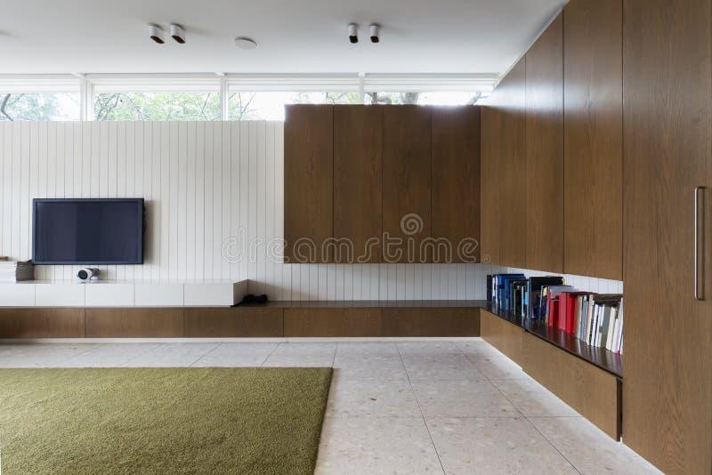 Nowożytny żywy pokój z orzechów włoskich gabinetami i tv zdjęcia stock