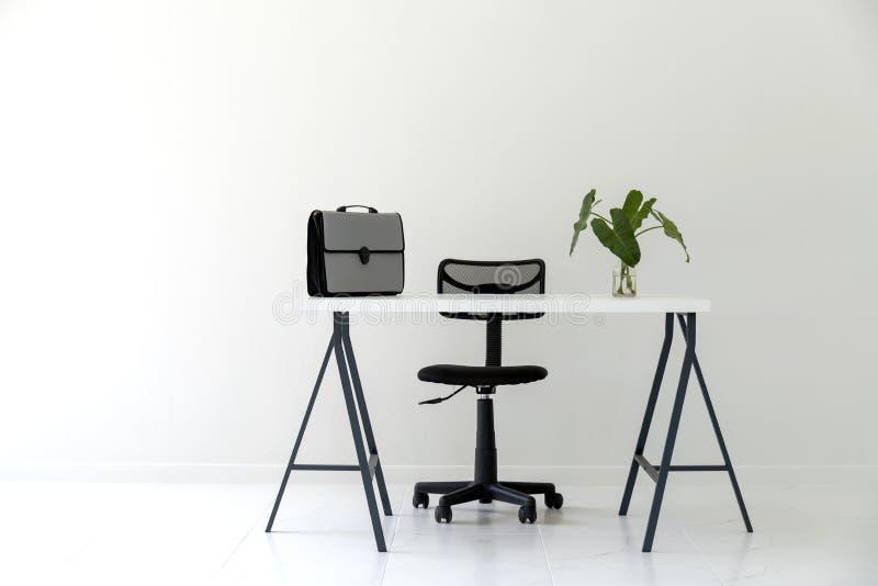 Nowożytny biały biurowy wnętrze z bielu stołem, czarnym krzesłem, dokument torbą i zieleń liścia wazą, obraz stock