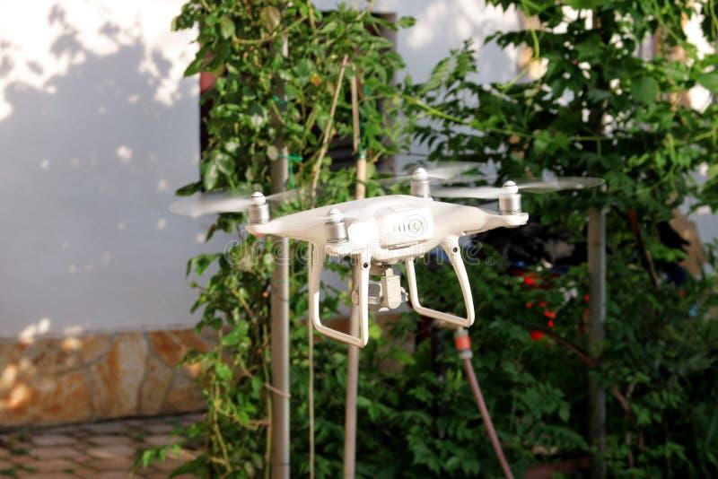 Nowożytny Biały kwadrata copter truteń z 4K cyfrową kamerą lata w powietrzu brać fotografie i dokumentacyjnego materiał filmowego obrazy stock