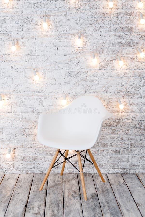 Nowożytny biały plastikowy krzesło w loft białego pokoju wnętrzu z drewnianą podłoga Żarówki girlanda na białym ceglanym tle zdjęcia stock