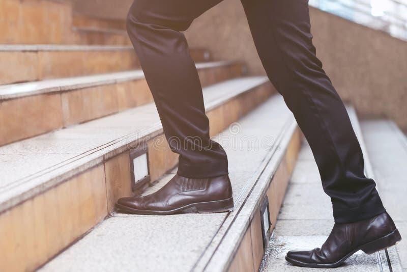 Nowożytny biznesmen pracuje w górę nóg chodzi w górę schodków w nowożytnym mieście mi?kkie ogniska, zdjęcie stock